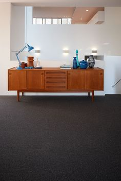Contemporary interior architecture & a contrasting charcoal berber style wool loop pile carpet are the perfect setting for a retro side board and classic blue accessories create a cool Mid-Century look! Credits – Carpet: Godfrey Hirst Carpets; Lamp: Amalfi; Wooden Vessels: Luke furniture; Glass Vessel: Amalfi.