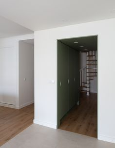 Lola Cwikowski Studio has overhauled the Carnide Apartment in Lisbon to feature minimalist interiors that offset the hectic lifestyles of its owners. Minimalist Apartment, Minimalist Interior, Lisbon Apartment, Tall Cabinet Storage, Locker Storage, Central Table, White Sideboard, Minimal Kitchen, Entryway