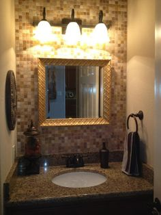 Pinterest Inspired Half Bath Remodel, Our half bath used to have a pedestal sink. We removed it and replaced it with a vanity to give us more storage and counter space. We added Travertine tile to the back wall, a framed mirror and new light fixture. , We hung a gold framed mirror to compliment the tile and granite. We added an iron light fixture that holds 3 bulbs instead of 2. , Bathrooms Design