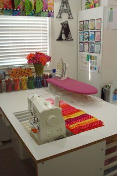 Craft room inspiration-I love the idea of havng my sewing machine face out into the room instead of having it face the wall!