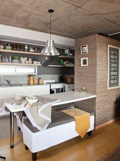Cocina comedor integrada con una barra en un departamento chico de San Fernando. La lámpara galponera y revestimiento de paredes aportan un toque rústico. Foto: Javier Csecs