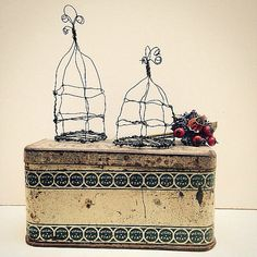 A pair of teeny tiny, winky wonky handmade wire art birdcages made from florists wire and the perfect size for your paper doll, or alternatively