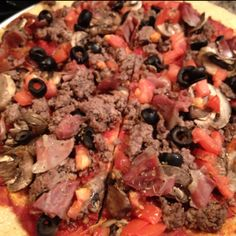 Paleo pizza made with a almond meal crust topped w/ ground sirloin, prosciutto, mushrooms, tomatoes and black olives.