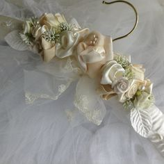 A beutiful padded dress hanger ,ideal for your wedding gown,Arranged with hand made ribbon and fabric roses.