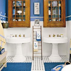 7 Beach-Inspired Baths | Antique Coastal Bathroom | SouthernLiving.com  Above the two 1900s pedestal sinks are two oversize glass-front cabinets found at an antiques store. The combination of the blue, white, and yellow with the dark wood gives a nautical feel to this coastal bathroom.