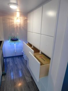 In this bathroom is an Ofuro soaking tub, a sink with a translucent LED-lit Corian stand, and a large storage wall with drawers and cabinets.