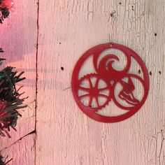This triathlon ornament features the Swim, Bike, Run symbols within a circle. It is made of steel and painted bright red. Weve been designing