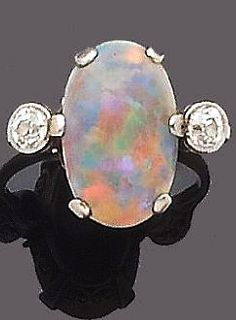 An early 20th century opal and diamond dress ring The cabochon opal, within a six-claw setting, between millegrain-set old brilliant-cut diamond shoulders ¤¤¤ What a fantastic opal! I've never seen colors like that or any color that rich. Beautiful