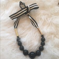 Nautical black necklace with bow This cute nautical necklace is black balls all around it and has a black and white ribbon to be tied in the back, very long!! At least 20 inches ! So cute to dress up any outfit! Not sure of brand! LOOKS BRAND NEW! No stains. No damages. No rips !! Jewelry Necklaces