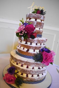 3 tiers of Naked victoria sponge cake with piped buttercream and raspberry jam, decorated with fresh flowers & fruit