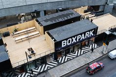 Boxpark is a unique shopping center built within shipping containers. You grab a coffee, hang out upstairs, and overlook the busy intersection.