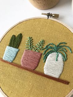 """A trio of colorful potted plants are hand-stitched in cotton thread on honey yellow linen, set in a 5"""" wooden embroidery hoop. One of a kind and ready to ship"""