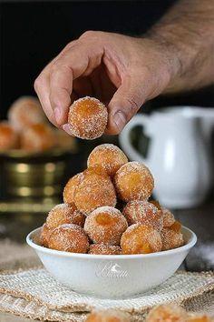 A recipe for Spanish buñuelos (similar to a fritter or donut hole) with caramel sauce | Receta de buñuelos de manzana y salsa de caramelo | devourtours.com
