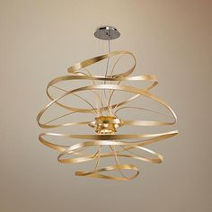 The Calligraphy LED pendant light by Corbett Lighting is a fluid metal form in s gold leaf finish with polished stainless accents.