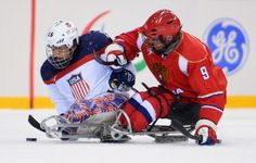 SOCHI, RUSSIA - MARCH 15: Nikko Landeros of the United States is challenged by Konstantin Shikhov of Russia during the Ice Sledge Hockey Gold Medal game between the United States and Russia on day eight of the Sochi 2014 Paralympic Winter Games at Shayba Arena on March 15, 2014 in Sochi, Russia.