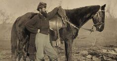 John E. Cummins of the 50th, 99th and 185th Ohio Infantry regiments poses in Union uniform next to a horse.