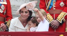 In the pink: Princess Charlotte, centre, made her balcony debut held by her mother Kate, left, and wearing a beautiful pink dress, while Prince George, right watched the planes eagerly