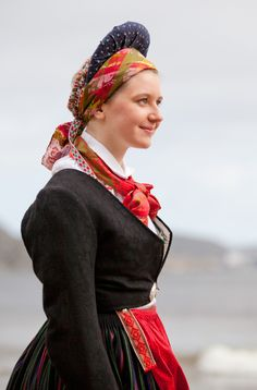 """The headdress that gives the Vest-Agder woman her silhouette is called """"valk"""" and when she marries she will wear a large white cotton kersheif tied over it. To keep the pleated waistline in place she wears red woven suspenders buttoned to her skirt by two forged silver buttons."""