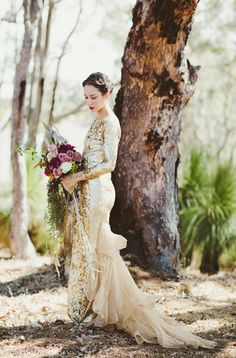 Sequined gold long sleeve gown worn with a bold berry lip and rich floristry in an intoxicating palette of plum
