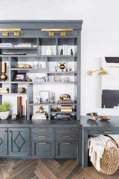 Alyssa Rosenheck - Nicole Davis Interiors boasts stunning antique blue cabinets with brass pulls and brass picture lights.