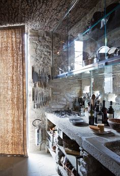 The guest-house kitchen has custom-glass cabinetry. The walls are original to the 11th-century structure, and the sink and countertop were made from 16th-century stone slabs. (Photo: Simon Watson)
