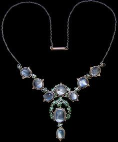 ESSIE M. KING (1875-1949) LIBERTY & Co. A silver and gold necklace set with moonstones within borders of blue/green enamelled leaves surrounded by gold wire wirework and gold florets. The silver chain with a gold clasp. British. Circa 1900. Size: Height of drop pendant only 4.4 cm. Width 2 cm. Width across three moonstones 11 cm. Total length around necklace 41 cm. Lit.: Liberty Style. Academy Editions. 1983. 'Glasgow Girls. Women in Art & Design 1880-1920'. Edited Jude Burkhauser