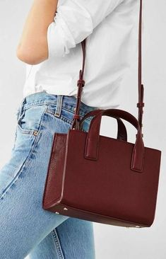 Structured mini tote bag in pebbled vegan leather with a long, removable shoulder strap, by Cooperative. Topped with short carry handles + zip closure trimmed w