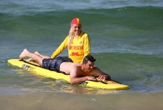The Los Angeles Dodgers' Drew Butera, bottom, rides a rescue board guided by surf lifesaver Sophie Thomson at Bondi Beach in Sydney, Wednesday, March 19, 2014. The Major League Baseball season-opening two-game series between the Los Angeles Dodgers and Arizona Diamondbacks in Sydney will be played this weekend. (AP Photo/Rick Rycroft)