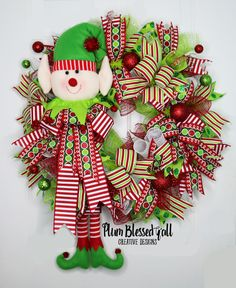 Everybody needs a little help sometimes, don't we?? Well Santa is no different! This Christmas Elf Deco Mesh Wreath celebrates Santa's crew of helpers in a fun and delightful way and will offer tons of good cheer hanging from your door for you, your family, friends and guest.