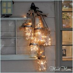 """Give your backyard a beautiful finishing touch with this rustic """"chandelier."""" Fill a few Mason jars with white string lights, and let the lanterns light up your night. Get the tutorial at All Things Heart and Home. Get more Mason jar ideas at Country Living. - GoodHousekeeping.com"""
