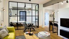 קיר זכוכית שקוף שמוסגר בריבועי אלומיניום שחורים מפריד בין חדר השינה לסלון, ומחליף את הקיר העבה ומלא הנישות שעמד במקום. צילום: בועז לביא
