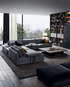 Bristol sofa in 412 cemento Rabat removable fabric, cushions in 1403 ocra and 1404 carbone Persia velvet. Bristol pouf in 1404 carbone removable velvet. Cenere oak Bristol coffee tables to be put behind the sofa and in the middle of the room.