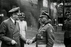 """Old friends: Adolf Hitler shaking hands with old comrade and once chief of his personal protection squad, SS Panzer Colonel-General Josef """"Sepp"""" Dietrich, after awarding him the Diamonds to the Knight's Cross with Oak Leaves and Swords outside the bunker at Hitler's HQ in Rastenburg.  The SS officer in white tunic is the SS liaison between Hitler and Himmler, Lieutenant General SS Hermann Fegelein. Two of Hitler's adjutants also attend. Aug 10, 1944."""