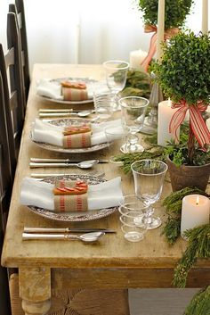 a rustic Christmas tablescape with an uncovered table, evergreens in pots, candles, refined chargers and striped napkins - DigsDigs Country Christmas, Winter Christmas, All Things Christmas, Christmas Holidays, Simple Christmas, Christmas Place, Natural Christmas, Modern Christmas, Christmas Morning