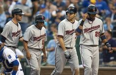 First baseman Joe Mauer #12 of the Minnesota Twins walks off the field with teammates Drew Butera #41, Ben Revere #11, and Pedro Florimon #25 after hitting a grand slam in the second game of a doubleheader against the Kansas City Royals at Kauffman Stadium on September 1, 2012 in Kansas City, Missouri.