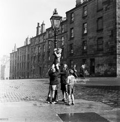 A group of boys help a companion climb a lamppost in a Glasgow street The inhabitants of Glasgow...