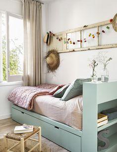 Pequeño dormitorio en tonos pastel claro y sombreros y guirnalda como decoración_00436803