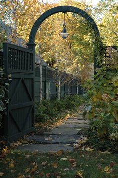 Love this fence and gate with archway.  The large flat stones make a great walkway, too!