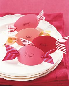 What could be sweeter or more simple? Cut out 3-inch ovals from colorful card stock. Using a hole punch, make a hole at each end, and then neatly write your guests' names on the ovals with black ink. Thread ribbon scraps, each about 6 inches long and 1 1/2 inches wide, through the backs of the place cards. Notch the ribbon ends, and set a card at each place setting.
