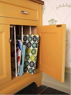 Tension rods can be used vertically to keep cabinet storage neat. | 30 Insanely Easy Ways To Improve Your Kitchen