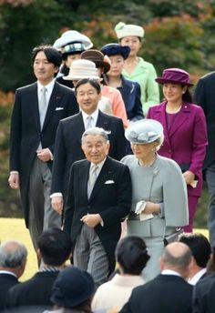 Japan's Emperor Akihito, bottom row left, Empress Michiko, bottom row right, Crown Prince Naruhito, second row left, Crown Princess Masako, second row right, Prince Akishino, third row left, and other royal family members walk down a hill to greet guests during the autumn garden party at the Akasaka Palace imperial garden in Tokyo Thursday, Nov. 12, 2015.