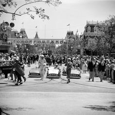 July 17, 1955 Crowds of people watch the Tomorrowland portion of a parade celebrating the opening of Disneyland.