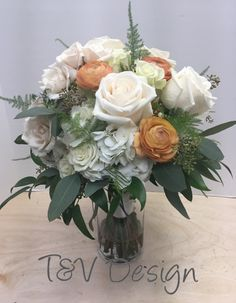 Mainly white bridal bouquet with orange ranunculus for a pop of color!
