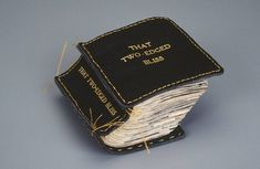 That Two-Edged Bliss by Lisa Kokin. Altered book pages, found images, leather, thread, 4 x 3.75 x 2.25 inches, 1999