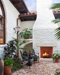 This Spanish-influenced home features a brick patio and a large stucco outdoor fireplace (via Lake Home Exterior - mediterranean - patio - austin - by Cornerstone Group Architects)
