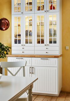 Nahaufnahme eines Schranks aus METOD Elementen, u. a. aus METOD Wandschränken mit 2 KROKTORP Vitrinentüren und 2 Schubladen in Elfenbeinweiß