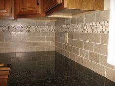 New kitchen backsplash with tumbled limestone subway tile and mixed mosaic accent
