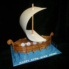 Viking Ship  Viking Ship Chocolate Mud Cake with Chocolate filling, coated in Dark Chocolate Ganache andFandant. Sail is Ivory Project Paper