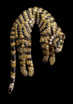 Tiger Clip Brooch, Cartier Paris, 1957. Yellow gold, single- and brilliant-cut diamonds ranging from fancy intense yellow to near colorless marquise-shaped emeralds (eyes) and fancy-shaped onyx (stripes). This piece is articulated. Sold to Barbara Hutton.