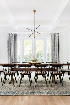 Bright midcentury modern dining space with a gold chandelier, and rectangular dining table and wooden chairs